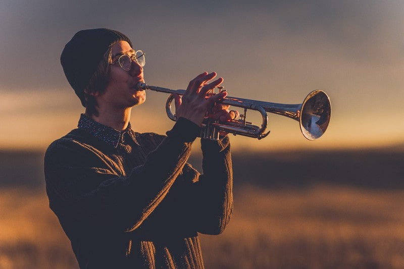 A young man playing a trumpet outside