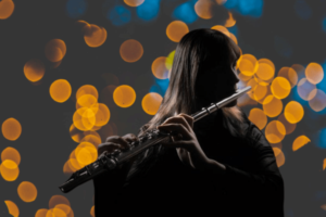 Flute player performing with lights behind