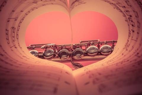 Heart-shaped music sheet with a flute in front
