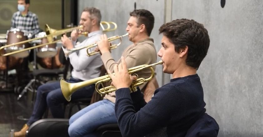 Two trumpet players and one trombone player performing
