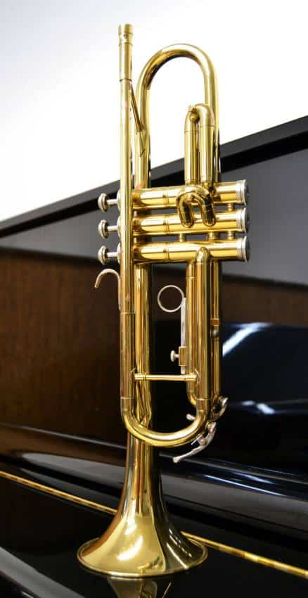 a brass trumpet above a piano 1
