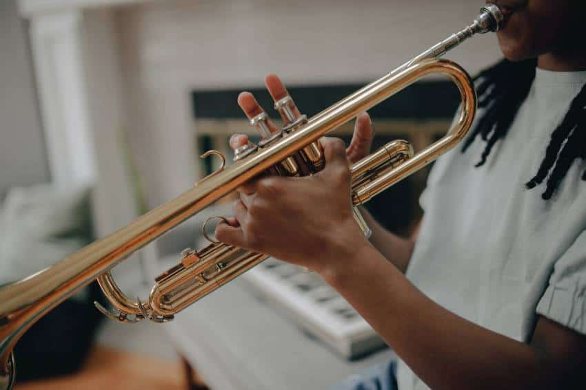 A beginner trumpet player performing at home